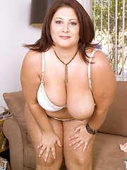 Brown-haired chubby woman licks her huge tits