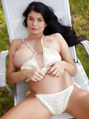 Lucy Li displays her big tits as she strips outdoors.