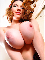 Busty redhead Kay strips and flaunts her big boobs
